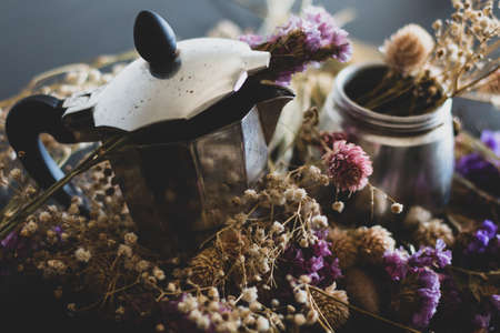 Coffee making concept. Ingredients for making moka coffee. Moka pot with coffee on dark background with a lot of colorful flowers. The coffee is in a vintage aesthetic composition.