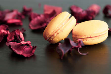 Close-up of breakfast morning with yellow macaroons lemon taste. close-up of french dessert on the black background and flowers around in a simple vintage composition. Food photography. Banco de Imagens
