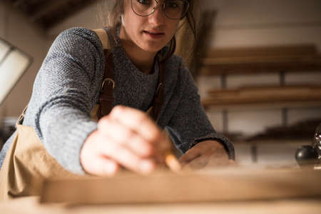 A young female carpenter working as wood designer in a small carpentry workshop. Young business woman handcrafting a piece of timber and designing new house furniture. Entrepreneurs concept lifestyle