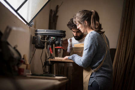 A young couple of carpenter working together in a small wood laboratory using a drill machine for timber. Couple crafting new home furniture in a carpentry workshop. young entrepreneurs concept 版權商用圖片