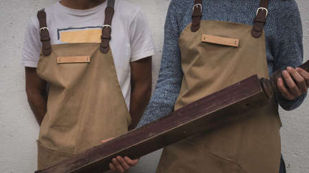 Close up of two young carpenters apron working in a small and familiar carpentry workshop. Entrepreneurs people working and running a business. Wood workers handcrafting in the laboratory
