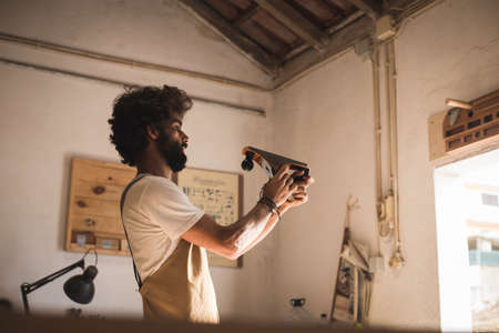 Hispanic man working as carpenter in a small wood laboratory. Bearded man concentrated on shaping a new piece of timber for a home furniture in his carpentry workshop. Entrepreneur people concept