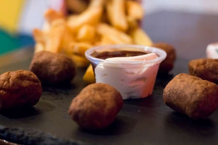 crispy fried chicken nuggets, fried meat cutlets rissole meatballs of minced pork and french fries on a wooden dark background. Simple fast food with different sauces.