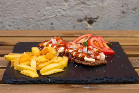 a mix of american fast food, junkie food. A fried meat like hamburger or beef steak with different sauces of ketchup and mayo with crunchy french fries, healthy tomato salad and a fresh mint beverage.
