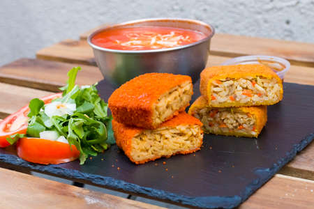 Classic, Italian arancini. deep fried Rice balls with minced meat and some vegetables inside. Tasty crunchy food with peanuts sauce and tomatoes soup with mozzarella cheese on the top. Close up view.
