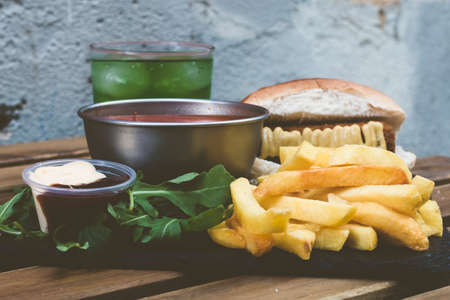 Unhealthy junk american food. A plate with french fries, fresh drink, salad, several sauces, a sandwich with bread and hamburger or meatballs, and tomato soup. All together on a wooden background.