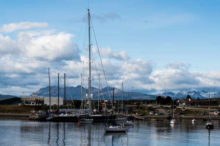 USHUAIA, ARGENTINA - April 04. 2018: Ships at the Port of Ushuaia, the capital of Tierra del Fuego, next to the little harbor town. Ushuaia is the southernmost city in the world Editorial