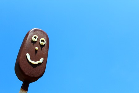 Ice lolly with face in front of blue sky