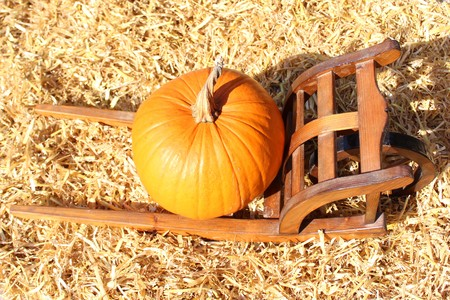 Halloween pumpkin on a wooden cart in the straw