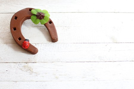 A rusty horseshoe with a lucky clover and a ladybug