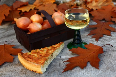 Onion cake, onions and a glass of white wine on a log in the forest Stock fotó