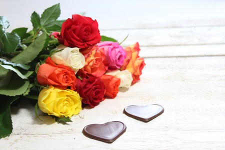 colorful roses with chocolate hearts