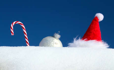 rock candy, christmas bauble and a Santa hat in the snow