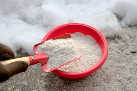a shovel with sand for winter service