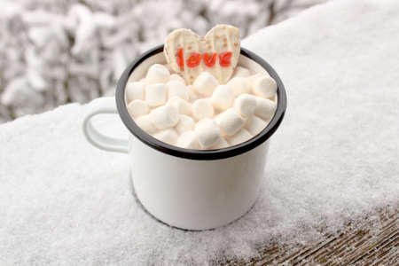 a cup with hot chocolate and marshmallow with a cake with the text love in the winter