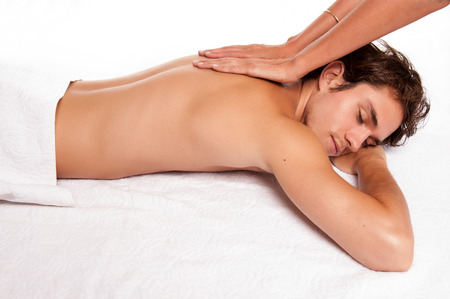Young male adult receiving a massage  studio shot  photo
