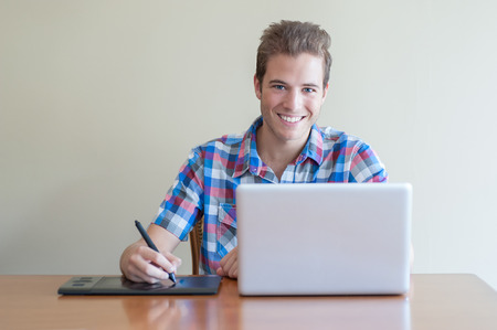 uncluttered: young male adult using computer and touch input tablet.