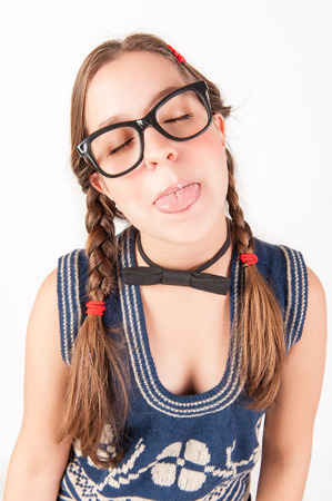 Young nerdy and goofy girl sticking out her tongue  studio shot  photo