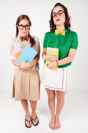 Cute nerdy girls holding books  looking at camera  Studio shot  photo