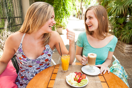 sitted: girl friends having fun sitted on a table Stock Photo