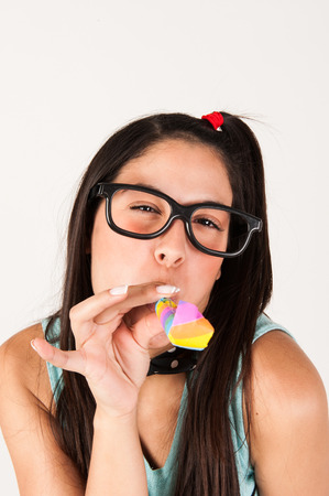 geeky: Cute nerdy girl blowing  a party horn  Studio shot  Stock Photo