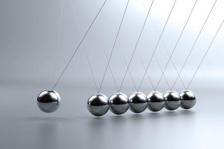 Metal pendulum balls balancing from strings in Newtons cradle photo