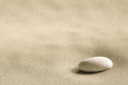 Close up of a small rock on a background of sand