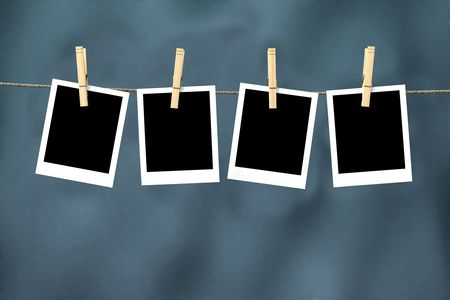 Four empty photos hanging from clothesline photo