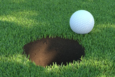 A white golf ball close to the hole Stock Photo
