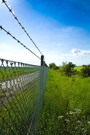 An endless fence with barbed wired separating fields photo