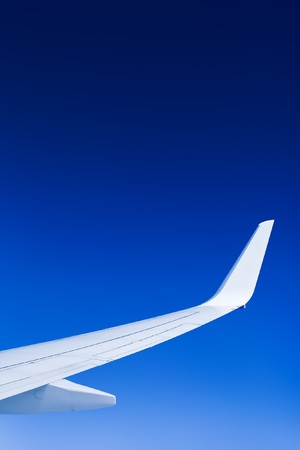 A bright airplane wing against a perfect blue sky.