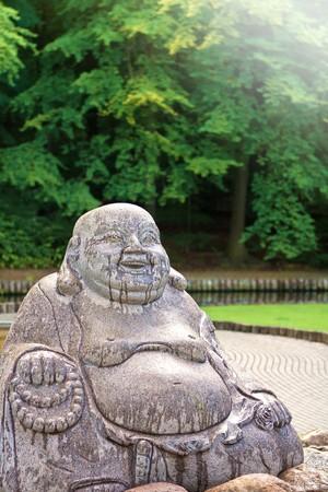 A fat granite Buddha statue in a park