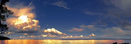 Beautiful golden glowing clouds reflecting in the sea Stock Photo