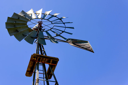 wind turbine at a well pump with a blue sky background