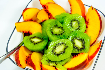 sliced fresh ripe kiwi and peaches ready to eat Imagens - 31028541