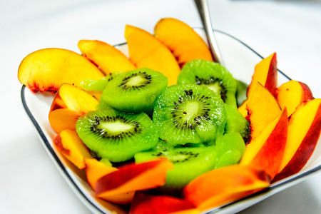 sliced fresh ripe kiwi and peaches ready to eat