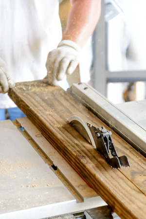 hand and tools doing wood work construction project with table saw