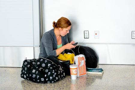 IAH, el Aeropuerto Intercontinental de Houston, Houston, TX, EE.UU. - Mujer sentada en el piso HTE cargar su teléfono en un aeropuerto