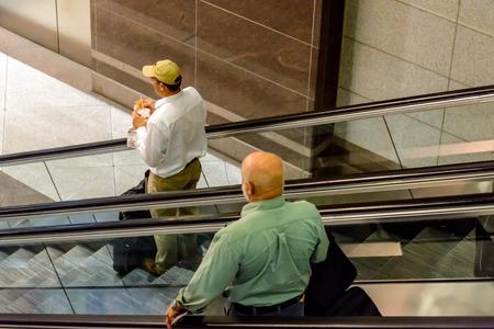 DIA, DEN, Denver International Airport, CO - People on escalators at an airport