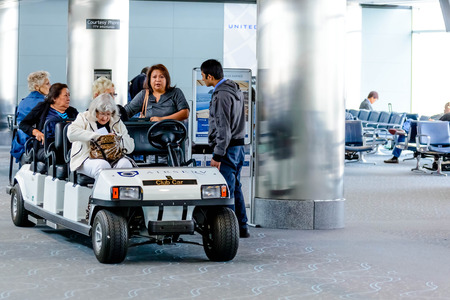den: DIA, DEN, Denver International Airport, CO - People and passengers riding in motorized carts in the airport