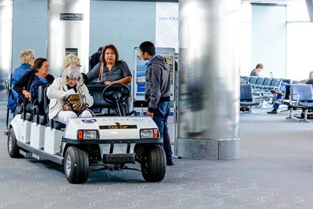 motorizado: DIA, DEN, el Aeropuerto Internacional de Denver, CO - La gente y los pasajeros que viajan en carros motorizados en el aeropuerto