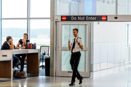 IAH, Houston Intercontinental Airport, Houston, TX, USA - flight personnel giving the thumbs up entering the boarding gate