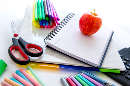 bright colored back to school supplies and an apple for the teacher photo