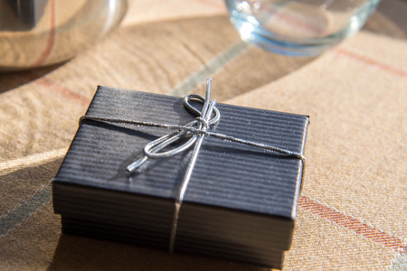silver jewelry: small black jewelry gift box with a silver bow in morning sunlight