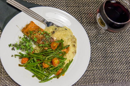 nutritious salmon dinner with green beans, mashed potatoes and roasted tomatoes
