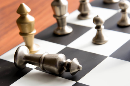 Classic chess game - fallen silver king on chessboard Reklamní fotografie