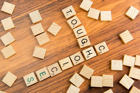tough: word board tiles spelling TOUGH CHOICES