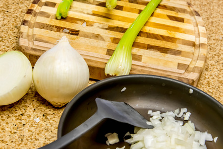 cook chopping celery on a cutting board