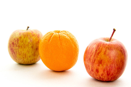 line of red and green apples with one orange Reklamní fotografie