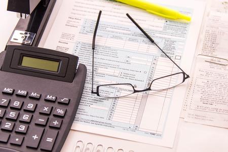 Fiscale voorbereiding benodigdheden, een leesbril en blanco belastingformulieren